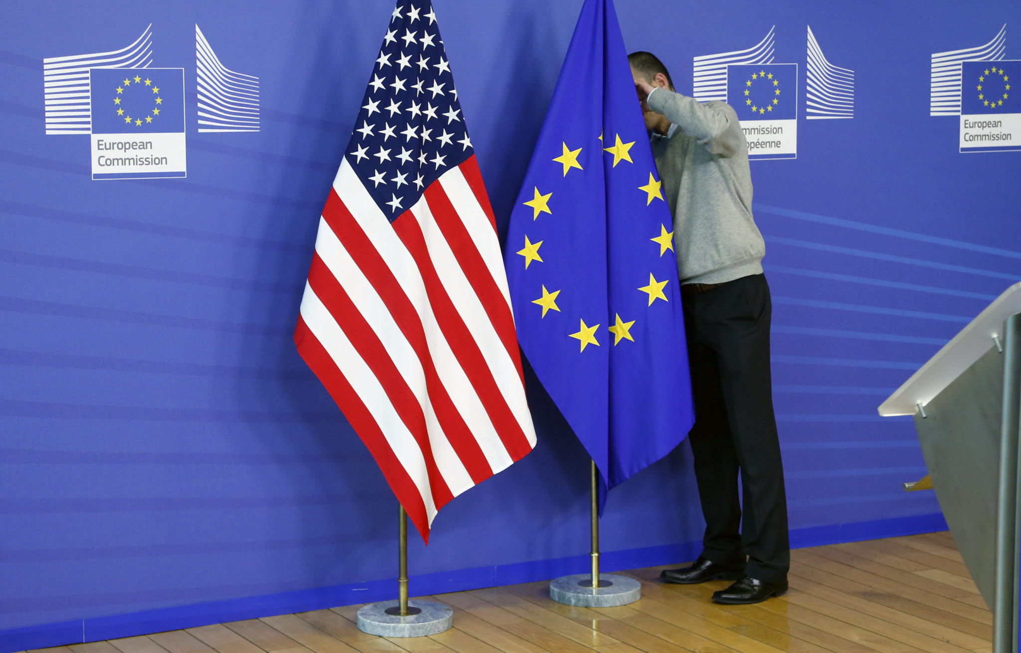 A worker adjusts European Union and U.S. flags at the start of the 2nd round of EU-US trade negotiations for Transatlantic Trade and Investment Partnership at the EU Commission headquarters in Brussels November 11, 2013. REUTERS/Francois Lenoir (BELGIUM - Tags: POLITICS BUSINESS) - RTX15919