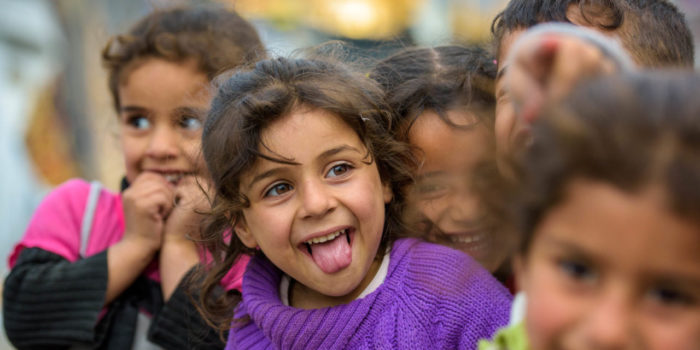 """Syrian refugee girl, Rahaff, 5, wearing purple sweater, is happy to be in a safe place. In an informal tented settlement in Bakaa, Lebanon.  Mom – Khadija Daughter – Rahaff, 5 Son – Ahmed, 2 (not in photos)   Khadija and her two children escaped from Syria to Lebanon five months ago. They came from a region that was under the control of militants who declared that no one was allowed to leave. Her husband paid a smuggler $250 so that she and the children were smuggled out through back country in a pickup truckload of sheep.   """"Food had become so expensive that we couldn't afford it,"""" says Khadija.   """"When they [the militant group] took control, they made many rules and changed them frequently to be stricter. It was very dangerous for women. If a woman got caught in public without a man from her family, she would be taken to the mosque. Then they would go to pick up the guys from her family and beat them, throw them in prison, or kill them.""""   """"It is much better for us here, even though we have no assistance,"""" she says. Khadija and her children share a tent with her husband's nephew and his family. Her husband stayed behind to take care of other family members."""